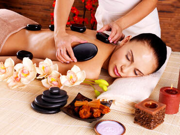 Woman getting a hot stone massage as she is laying down
