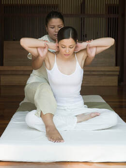 A woman giving another woman a Thai massage from behind